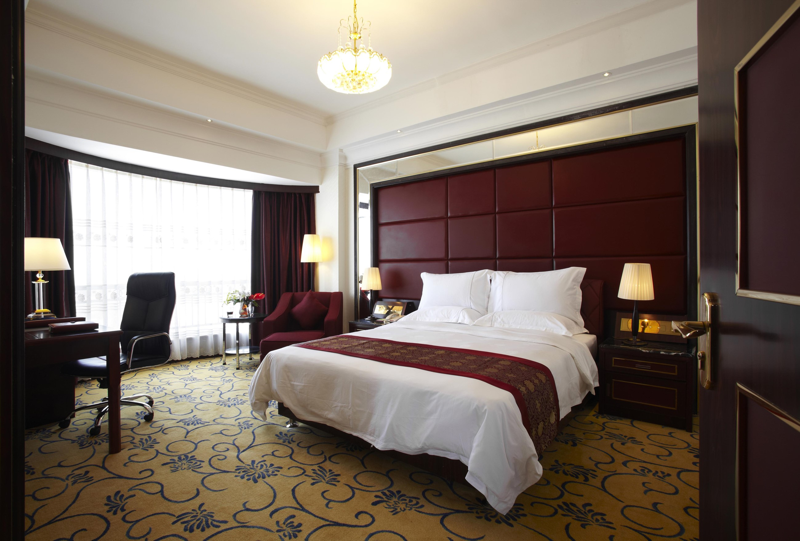 Photo of clean hotel room featuring king-sized bed, brown wood finish