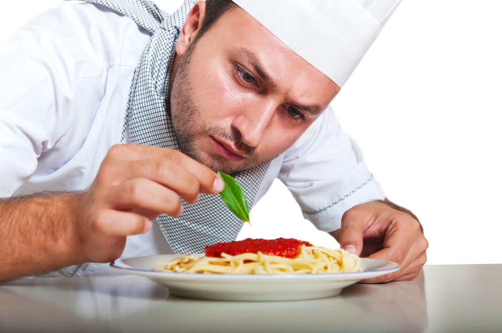 Photo of a male chef adding basil to a plate of pasta.